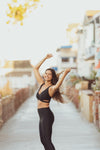 Model wearing Aura7 Activewear crisscross Malibu sports bra smiling with arms up on a sidewalk near the beach