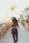 Model wearing Aura7 Activewear Vita legging yoga pants walking on a sunny sidewalk near the beach