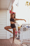 Model wearing Aura7 Activewear high waisted rigel shorts doing yoga pose on a balcony