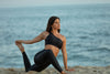 Model wearing Aura7 Activewear one shoulder Hermosa sports bra while doing yoga on the beach