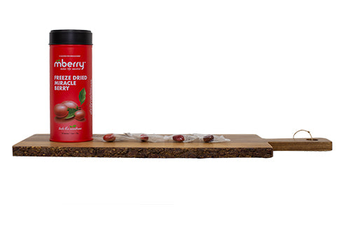 mberry freeze dried miracle berries on a wooden board with the miracle fruit lined up on the right of the packaging