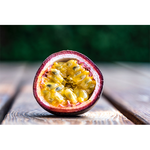 A cut passionfruit sitting on a wood desk with yellow inside and pink outside
