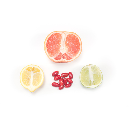 miracle berries with a lemon, lime, and grapefruit. Arranged in a triangle with miracle fruit in the middle