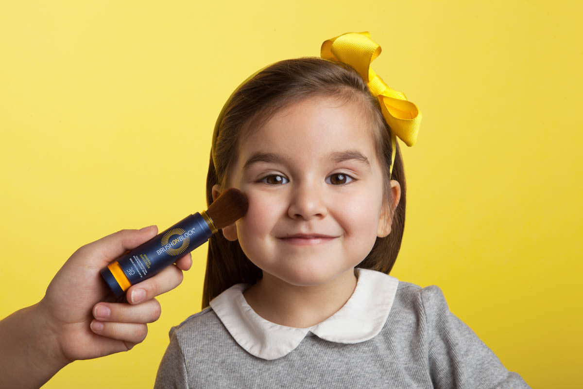small child with kid-friendly brush on block mineral sunscreen