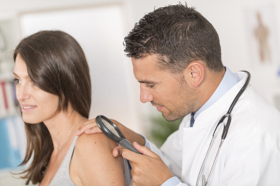 Brush On Block image of doctor examining mole on woman's shoulder