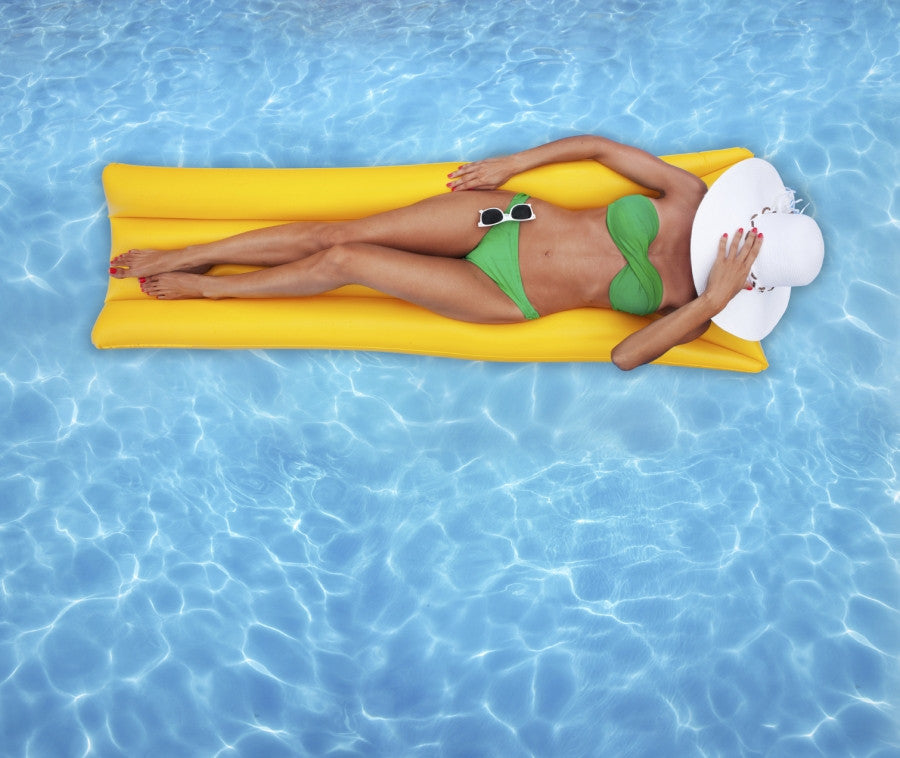 Brush On Block image of tan woman in bikini with big hat floating in pool.