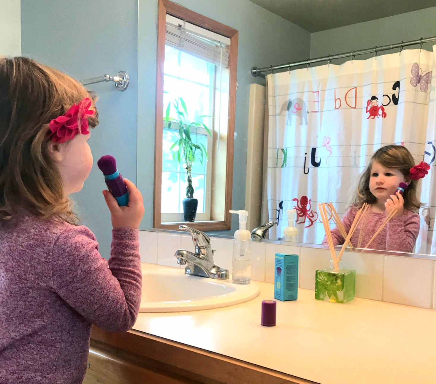 BRUSH ON BLOCK® image of girl applying BOB KIDS in bathroom mirror.