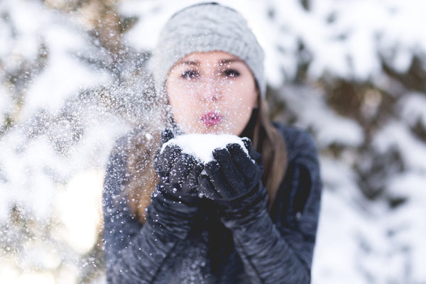 Brush On Block image of girl blowing handful of snow at camera