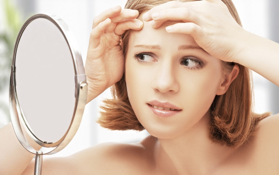 Brush On Block image of woman examining blemish in mirror.