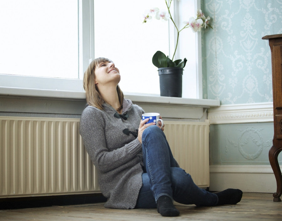 Brush On Block image of woman in sweater leaning on radiator