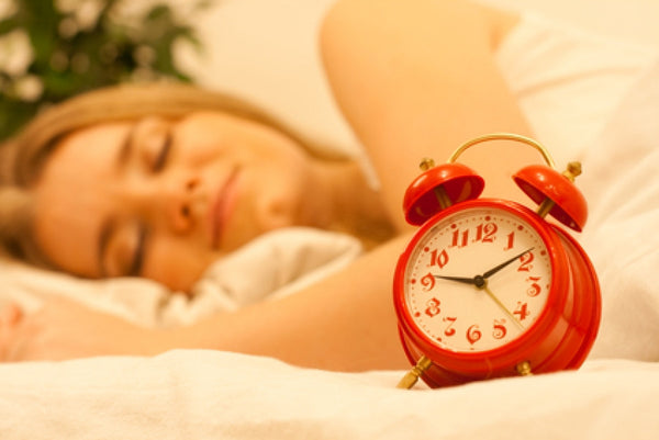Brush On Block image of woman sleeping with alarm clock in foreground.