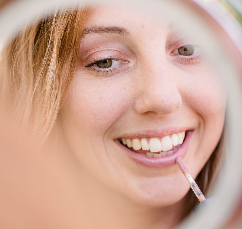 BRUSH ON BLOCK® image of woman applying Protective Lip Oil SPF 32