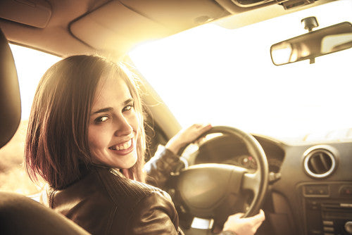 brush on block image of tanned woman driving in car smiling