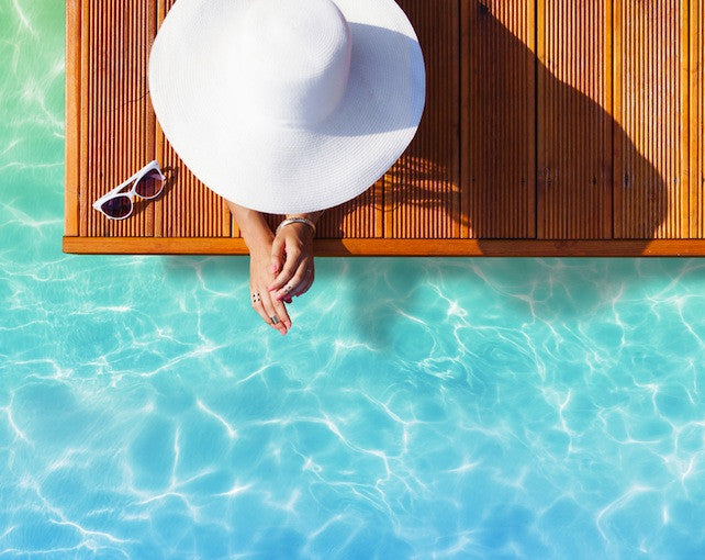 Brush On Block image of person laying poolside with large hat