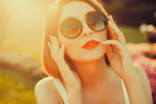 Brush On Block image of woman with red lipstick and sunglasses in the sunlight