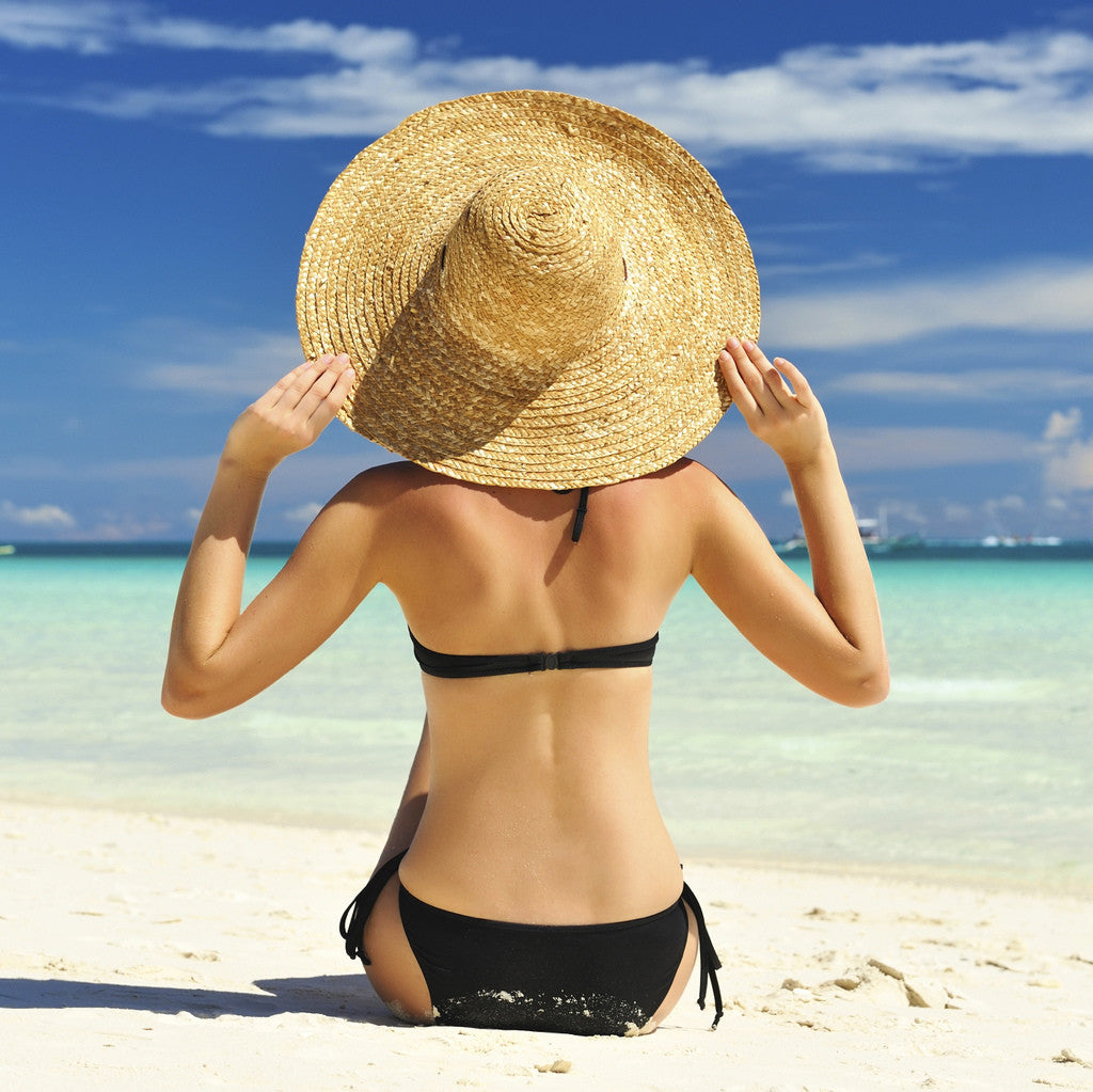 brush on block image of woman on beach in bathing suit and big hat
