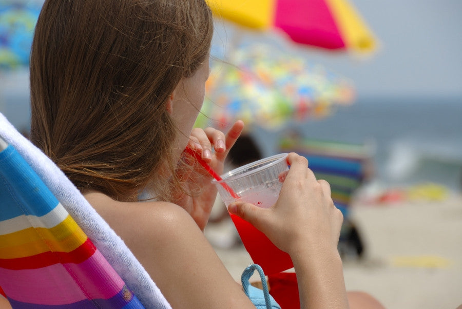 Brush On Block image of woman at beach drinking adult beverage