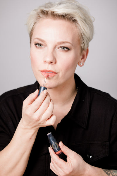 Blonde woman applying Protective Lip Oil SPF 32 in Coral.