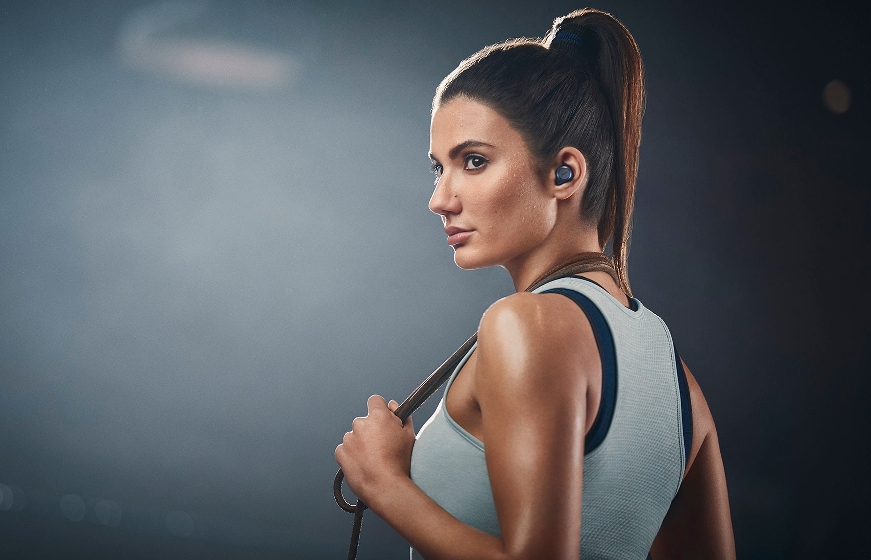 Jabra Elite Active 75t True Wireless Earbuds for Active Lifestyle - Female Model in sports gear looking back