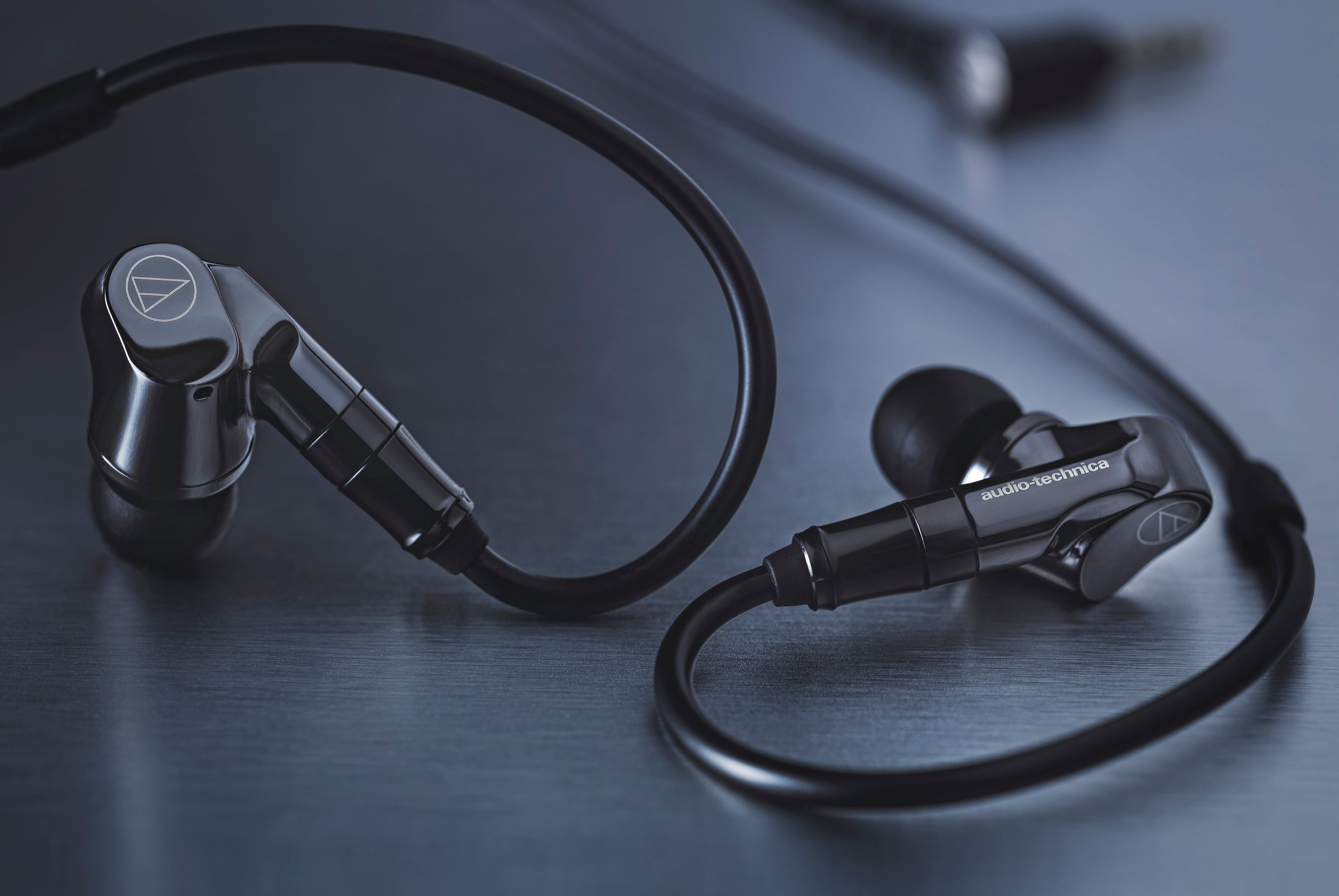 ATH-IEX1 In-Ear Hybrid Multidriver Headphones on the desk with beautiful reflections coming off the desk surface.