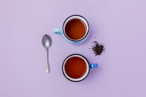 Two cups of organic tea on a lavender colored background