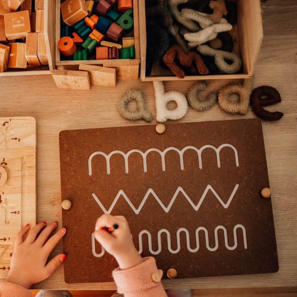 My First writing Pad By Qtoys | Montessori Range Our First writing pad is the perfect addition to encourage and build children with pre-writing. Each writing pad comes with one board that encourages straight lines, curves, and patterns, this is removable to place paper underneath and secured by 4 wooden nuts.