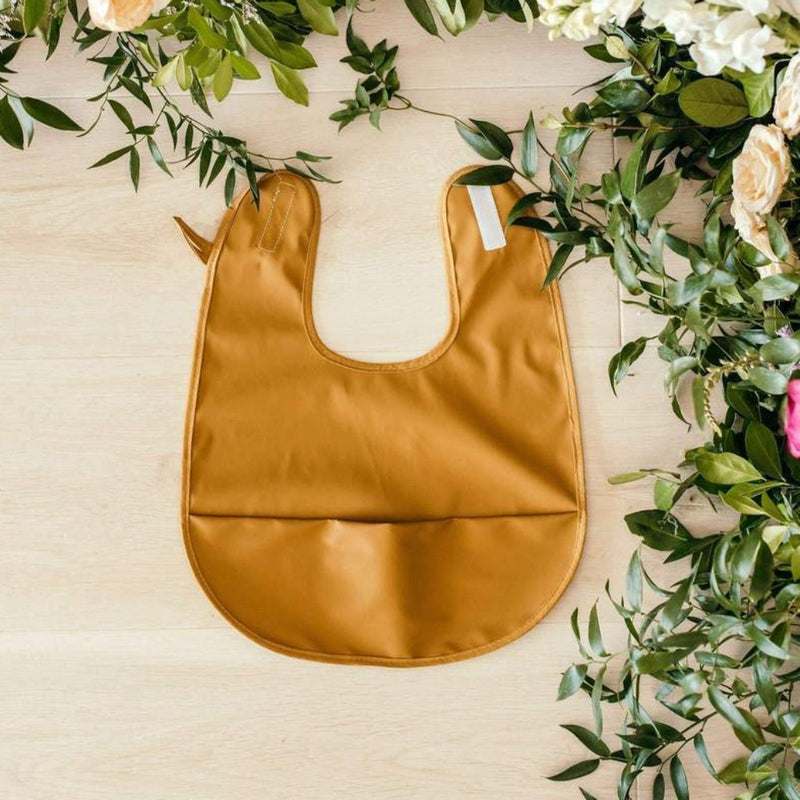 Byron Bronze bib by Snuggle Hunny Kids This sweet innovative Snuggle Bib comes in a deep Mustard | Bronze colour , It is a simple yet beautiful way to wear a bib on your baby. Keep mealtime mess to a minimum while making it fun and beautiful.  This would make the perfect baby gift or for the expecting mum. Bibs never looked so good!