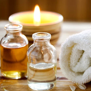 Essential oils on a table at a spa with towel linen and candle wax scent