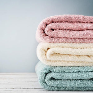 Fresh folded laundry towels washed with fabric softener detergent wax scent