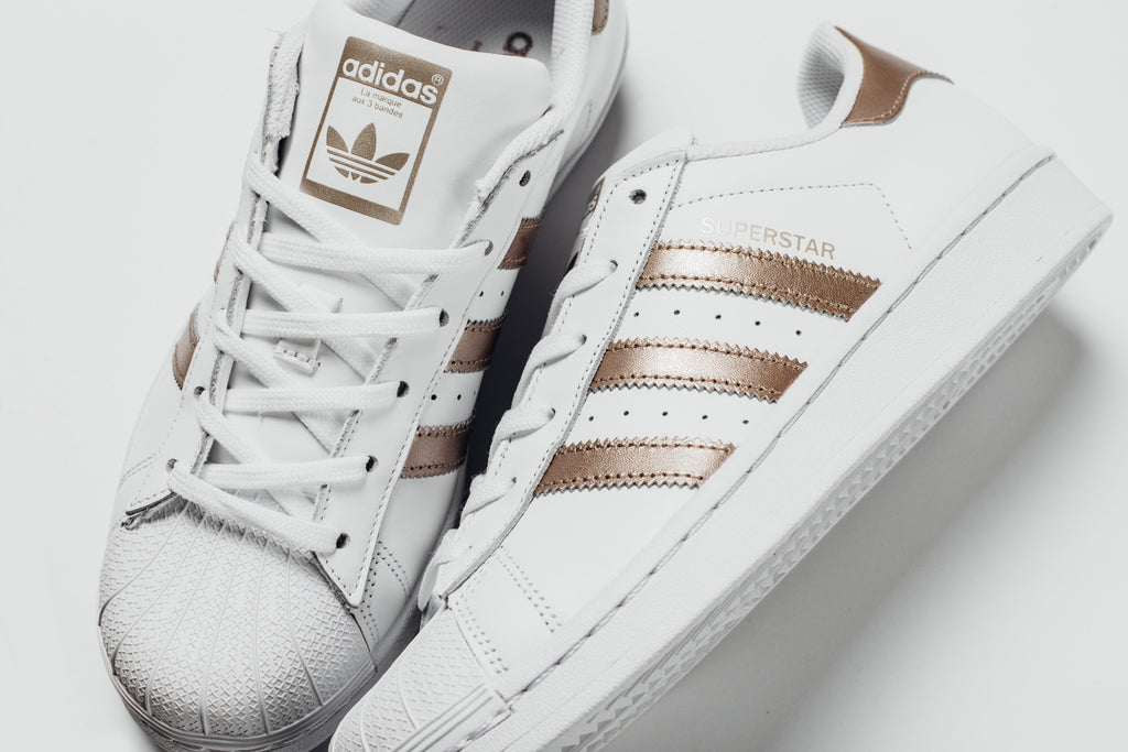 Adidas expands their Superstar collection, with a summer rendition for the ladies. The iconic silhouette ($80) showcases a white leather upper with bronze ...