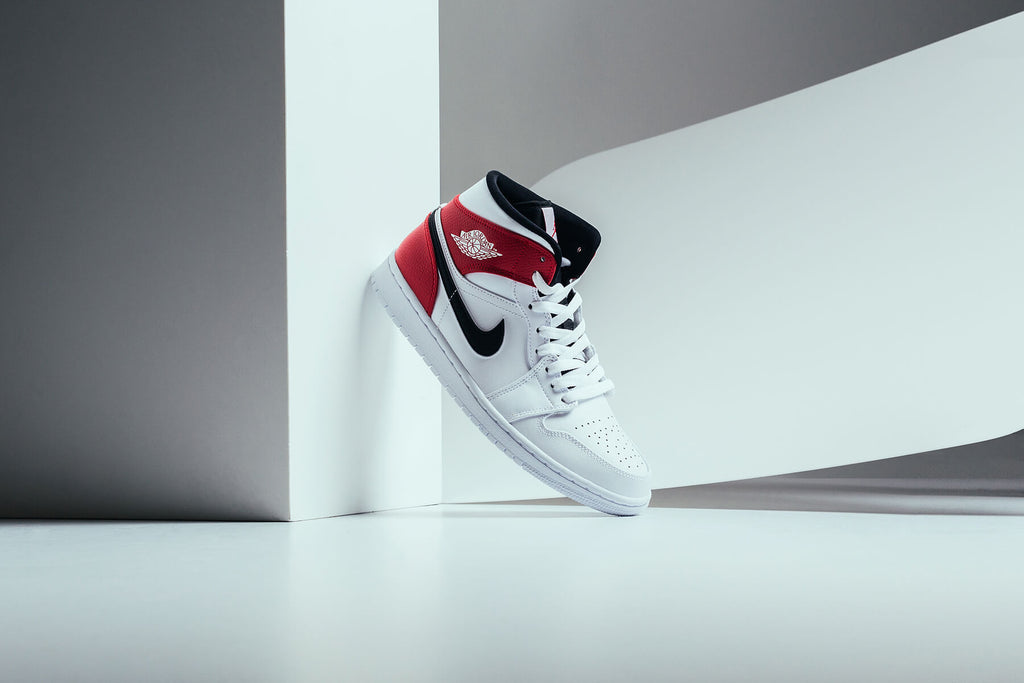 6c67bbcd31b Jordan Brand continues their Jordan 1 Mid line with a white, black, and gym  red rendition ($90). This time around we see the sneaker dawned with a full  ...