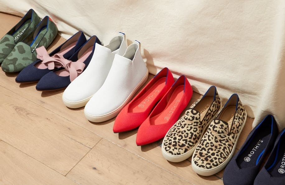 A lineup of solid and patterned Rothy's shoes on a wooden floor.