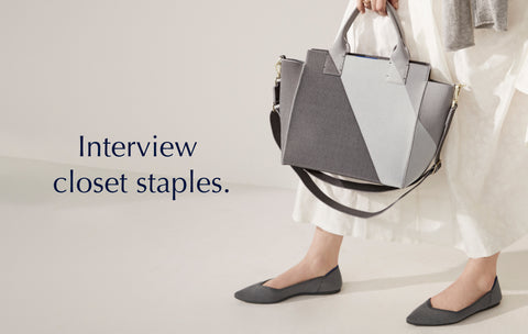 """Text saying """"Interview Closet Staples"""", against a background image of a model holding The Handbag in Charcoal Grey."""