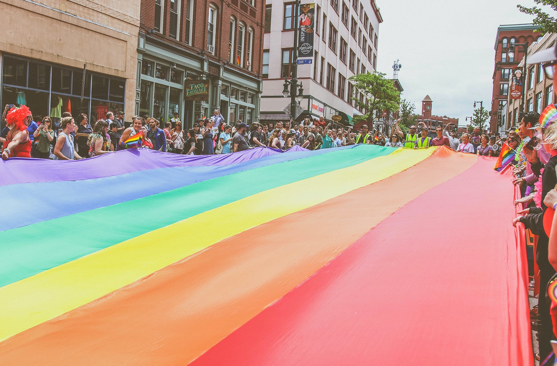 A big group of people holding a large pride flag in downtown San Francisco.