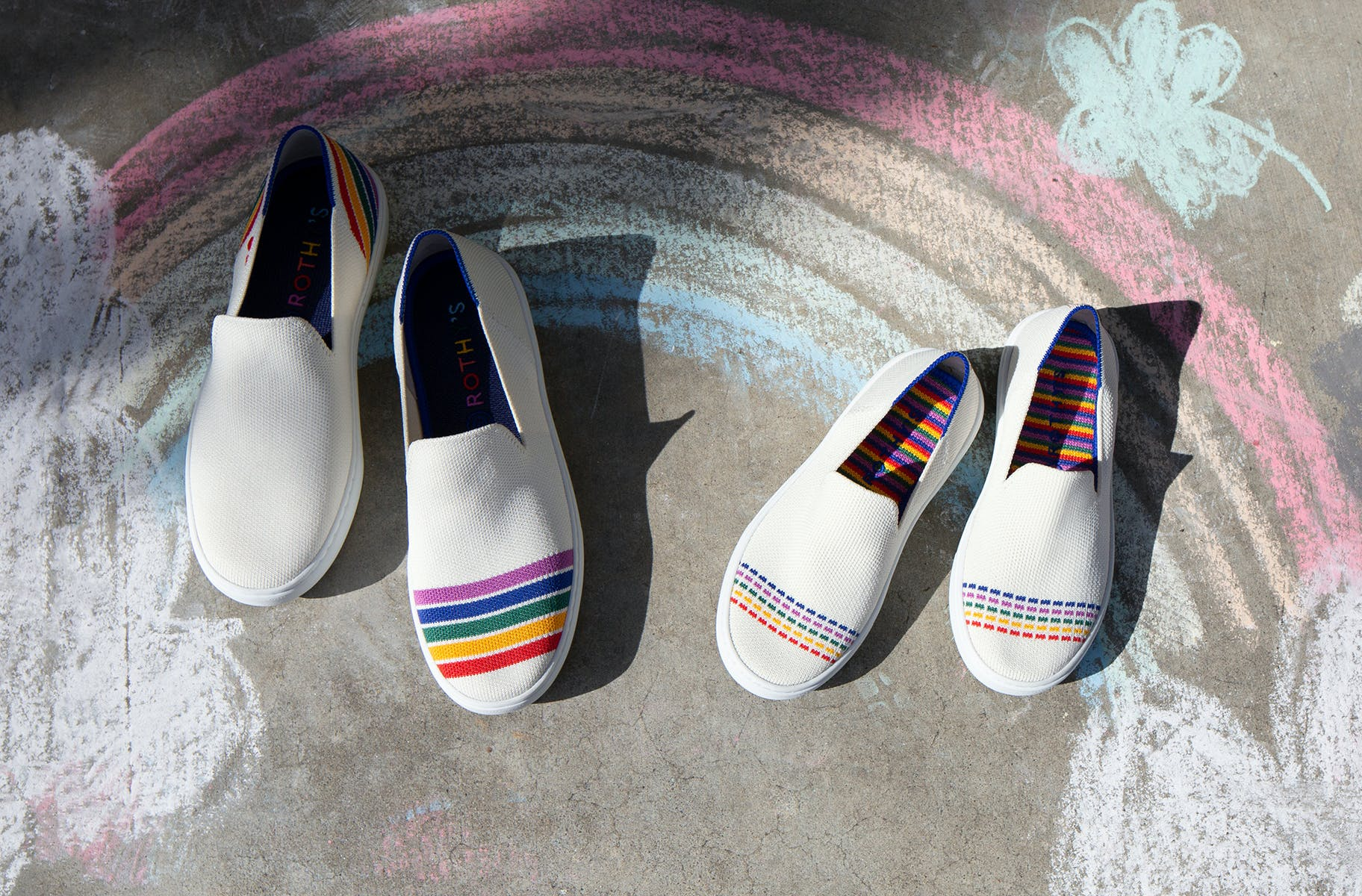 An adult's sneaker in white with multicolored stripes, and The Kids Sneaker in White Rainbow, shown on a sidewalk.