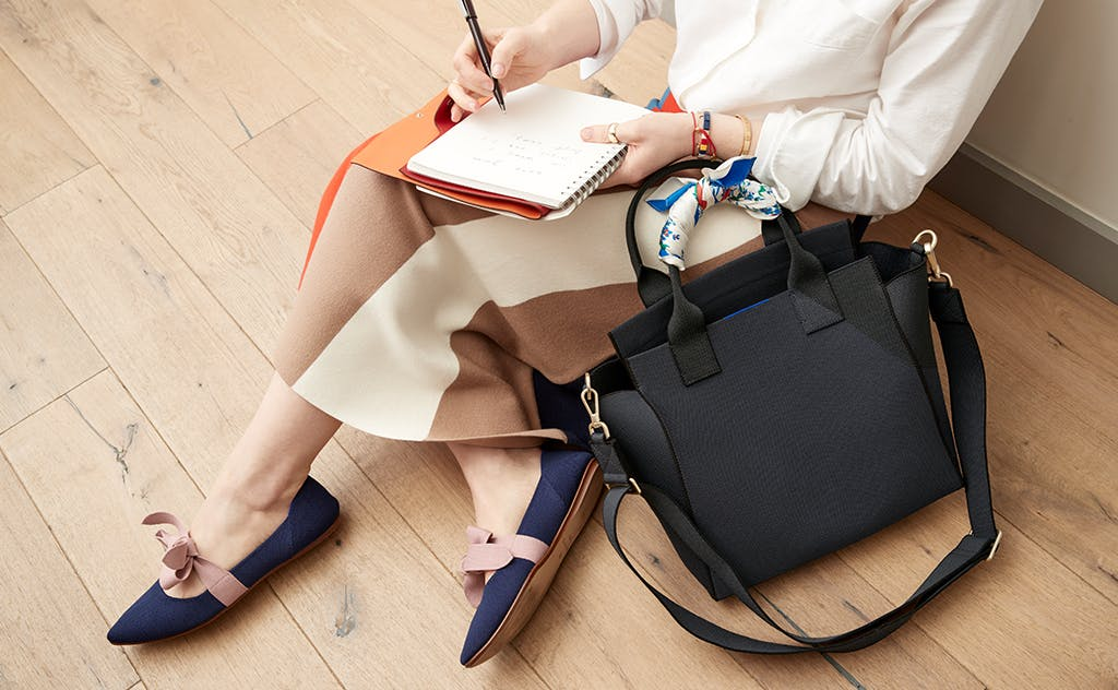 Art Director Gretchen sitting on a wooden floor while sketching in her notebook, with The Handbag in Midnight Navy next to her.