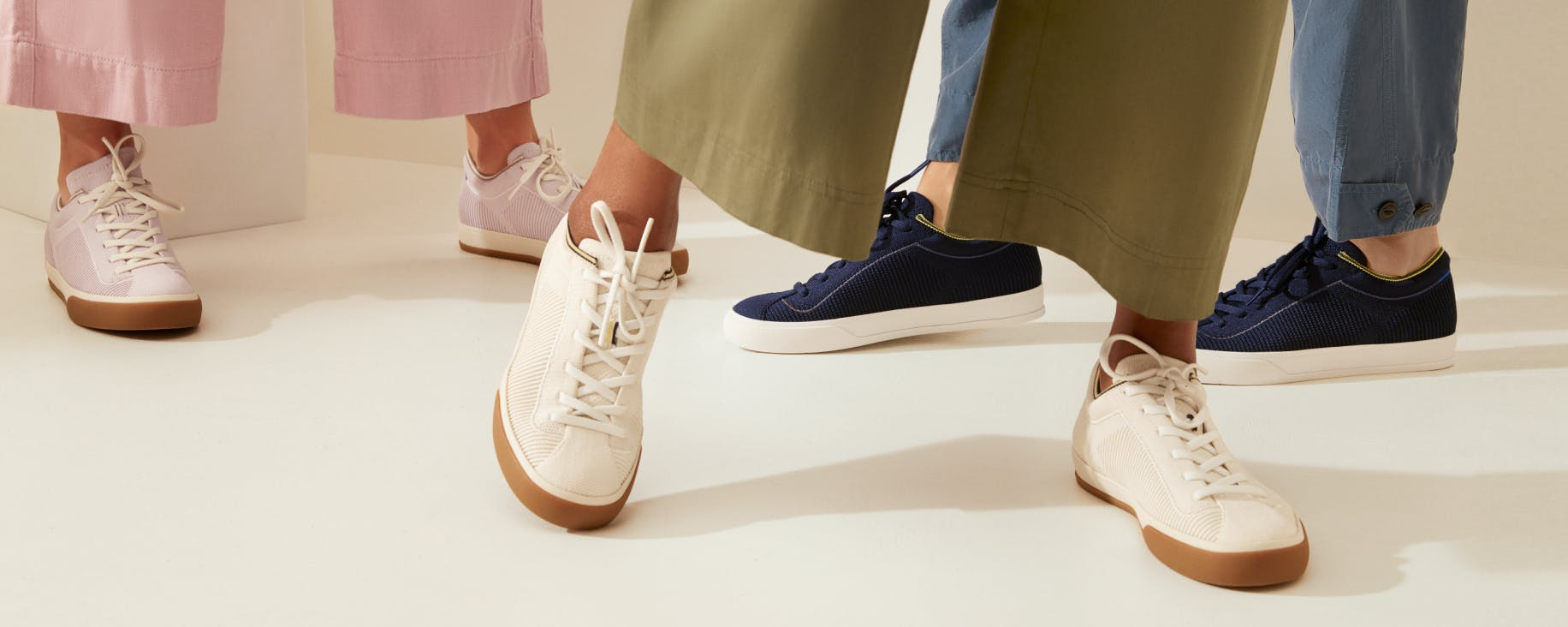 The Lace Up in Lilac, The Lace Up in Vanilla and The Lace Up in Navy shown on the feet of three models.
