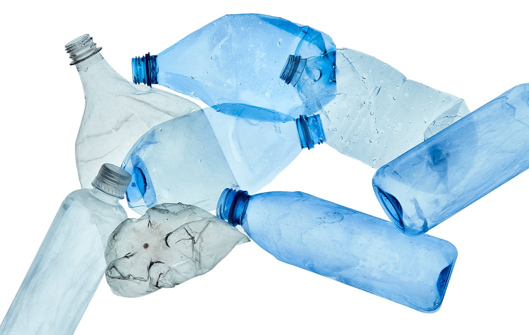 Close up of flattened blue and grey plastic bottles.
