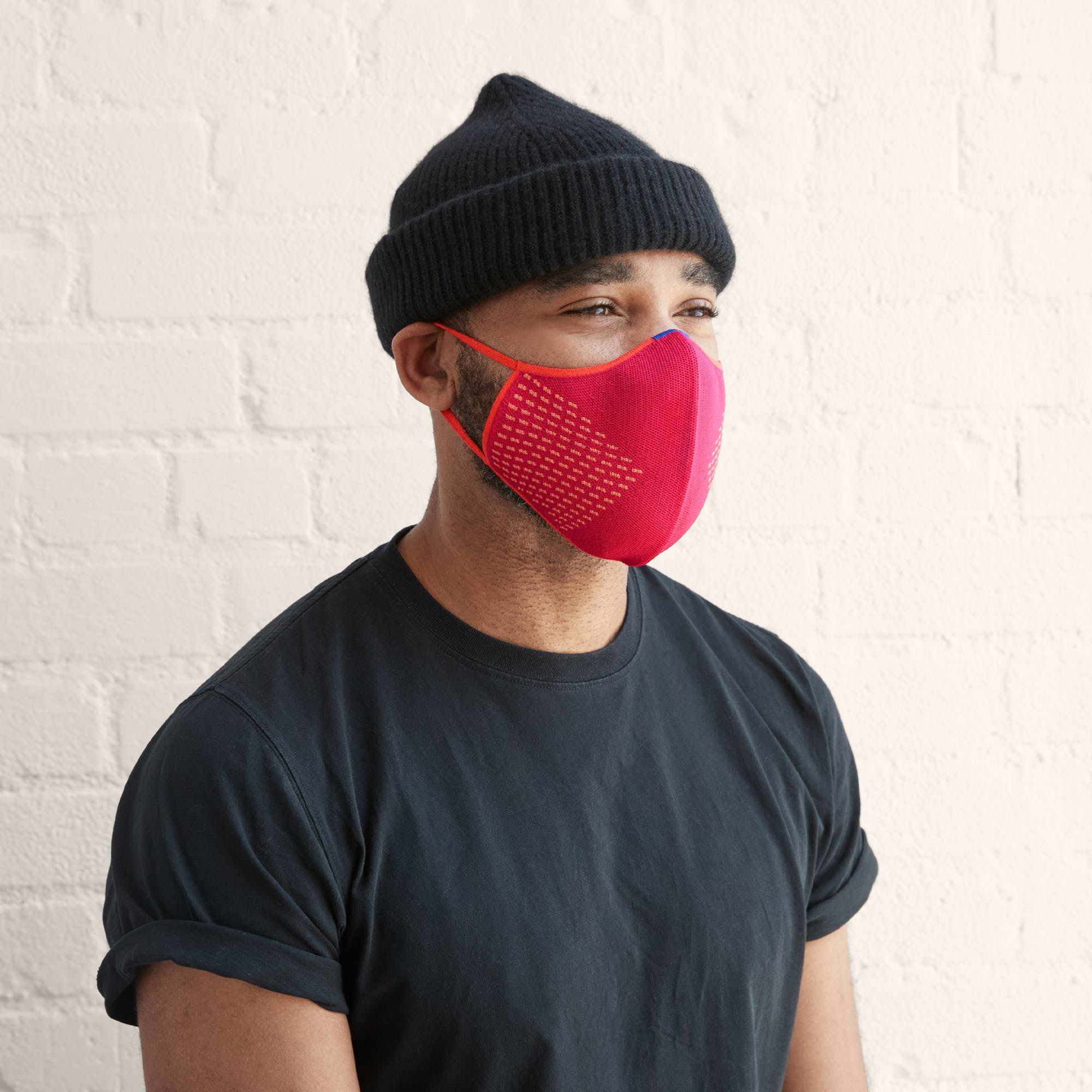 Man shown wearing a bright pink mask with light orange stitching details on the side.