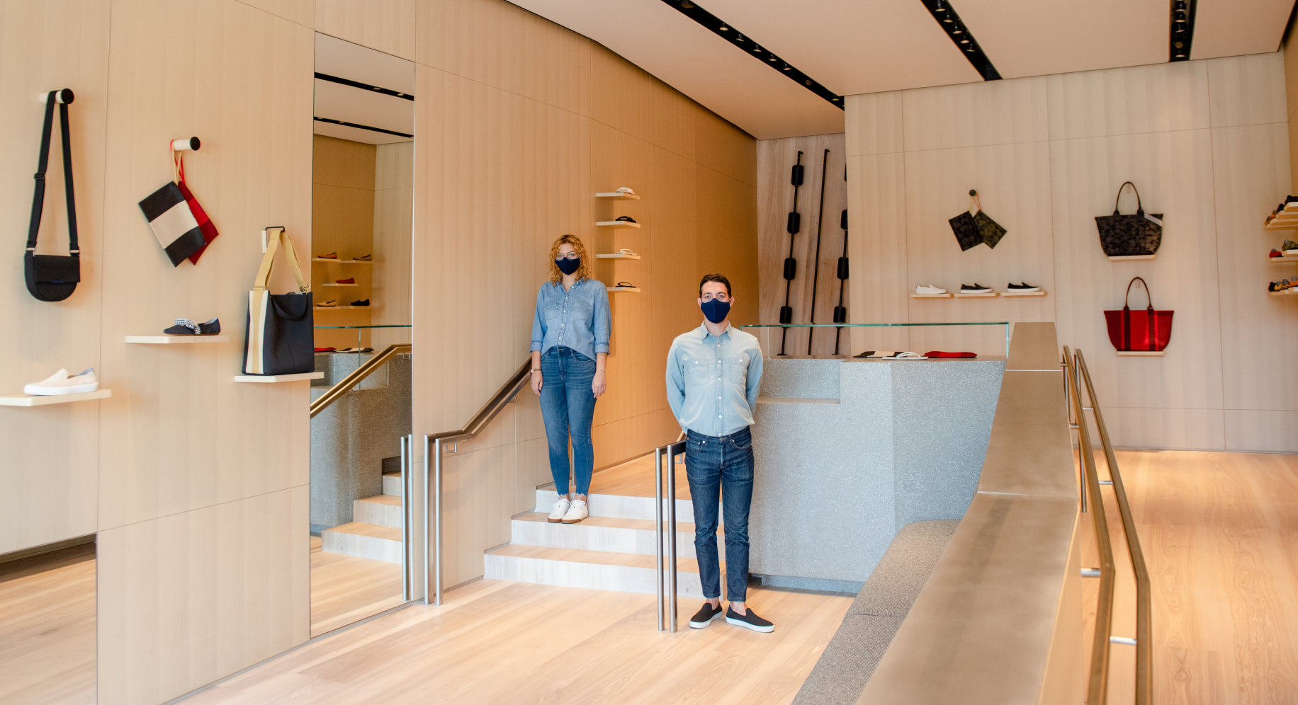 The interior of our store at Melrose Place, with two store associates wearing masks.