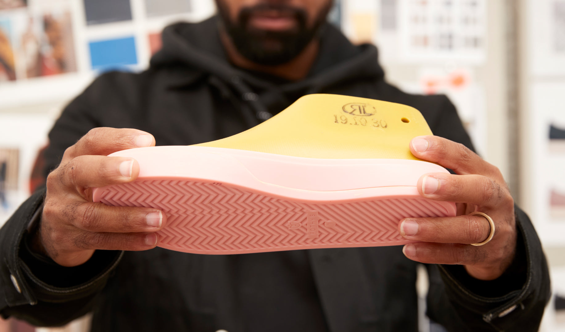 Close up of Lavion holding up a shoe prototype.