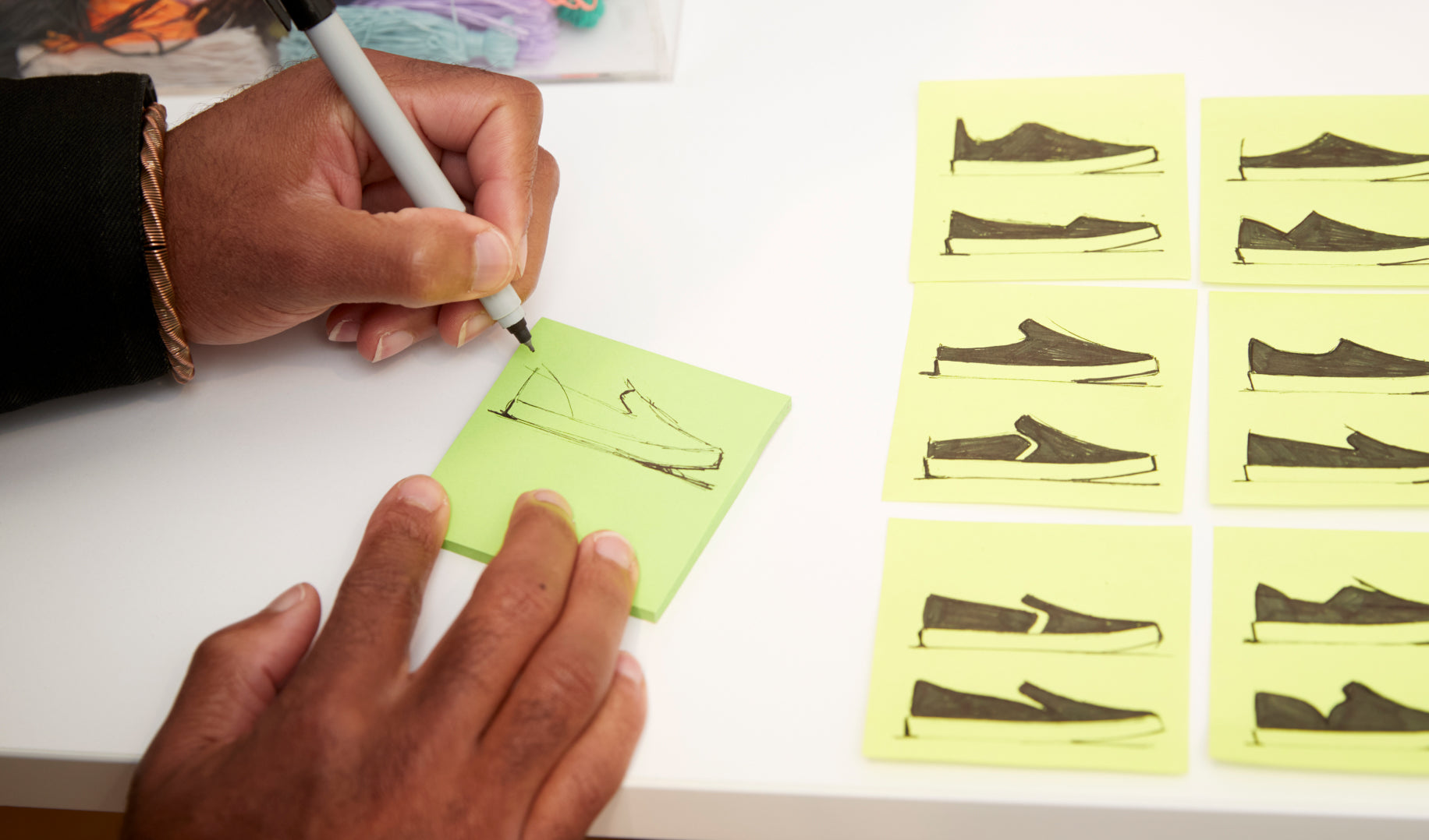 Close up of Lavion sketching designs of The Sneaker on post-it notes.