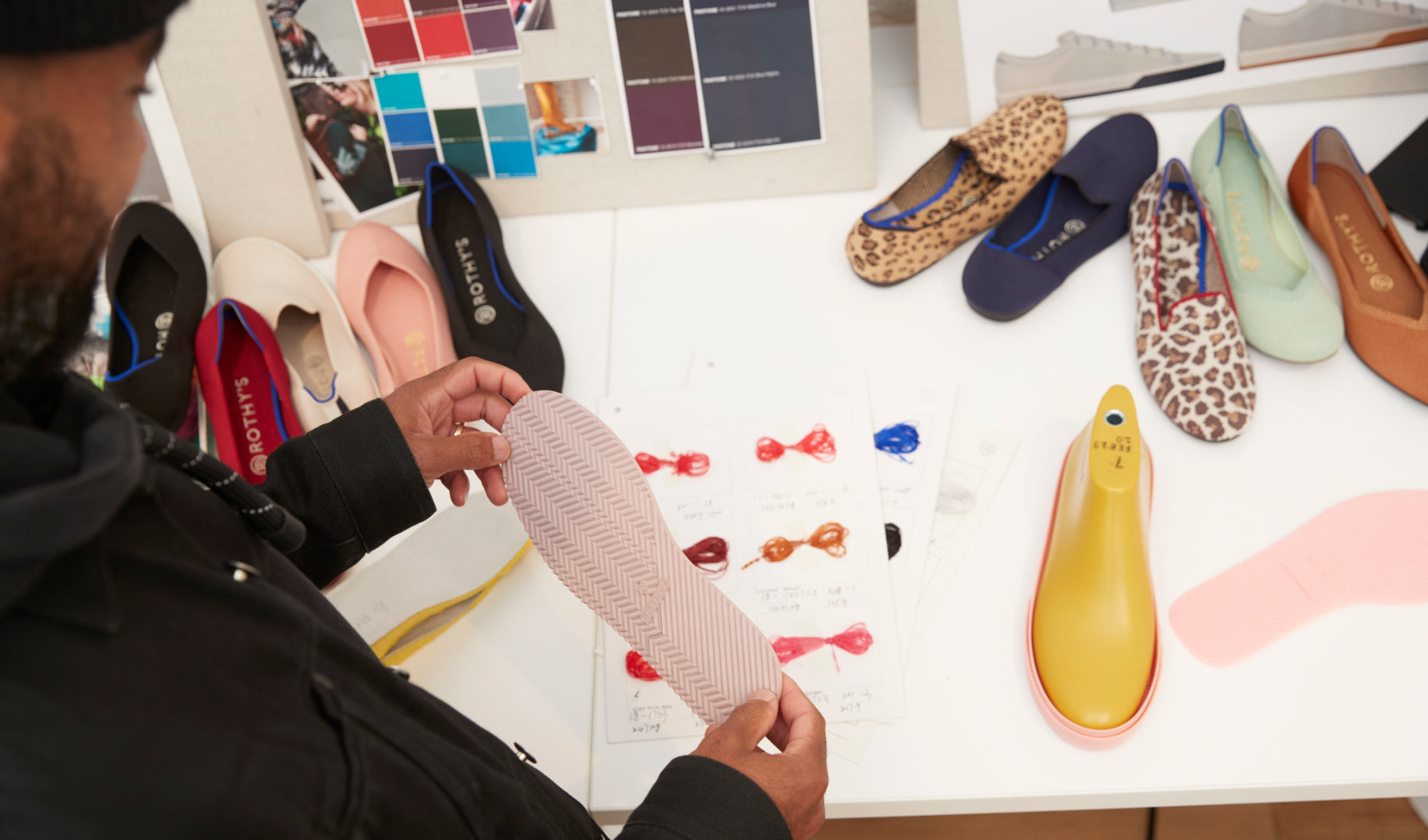 Lavion holding a light pink shoe outsole in front of a table with shoes and design materials.