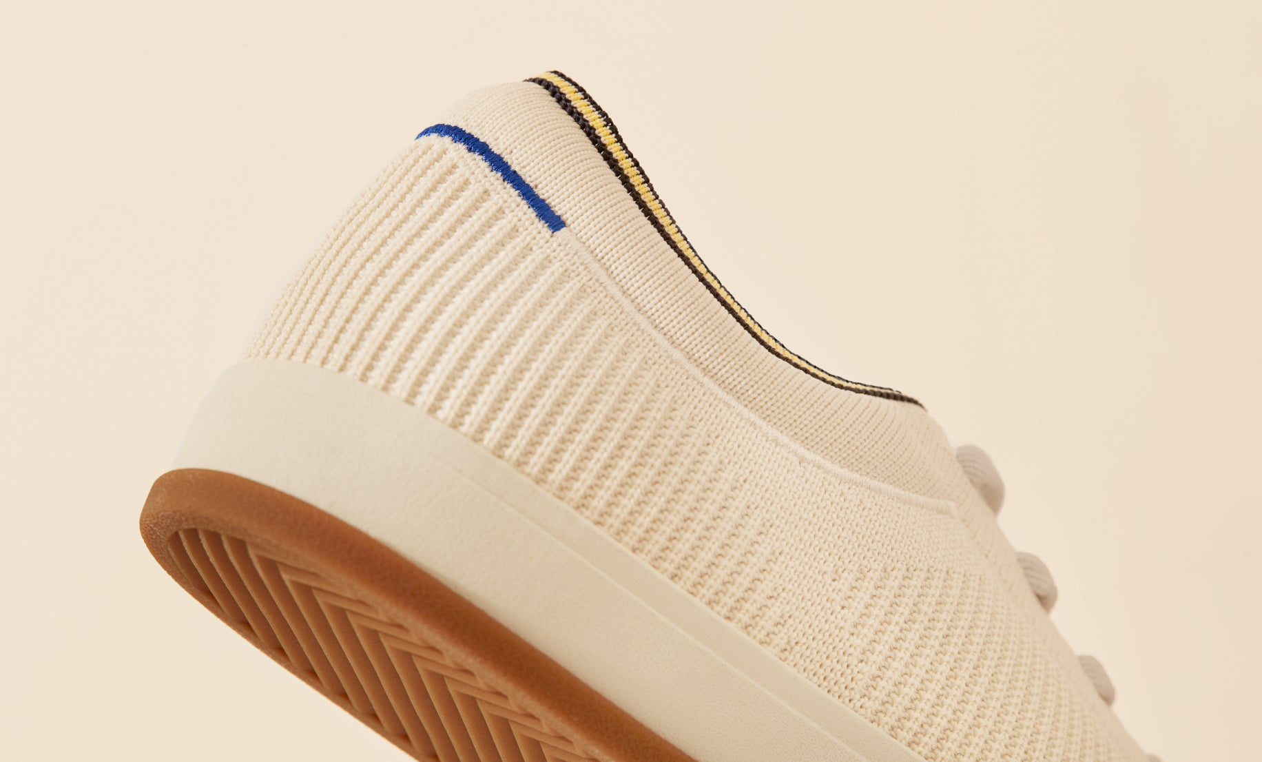 Close up of the heel area of The Lace Up in Vanilla, showing the Rothy's blue halo detail, plush ankle collar and gum outsoles.