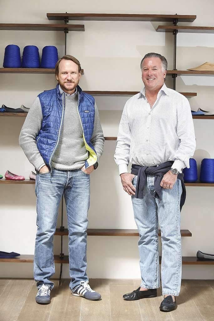 Co-founders of Rothy's Roth Martin and Stephen Hawthornthwaite, standing in front of shelves with spools of thread and shoes upon them.