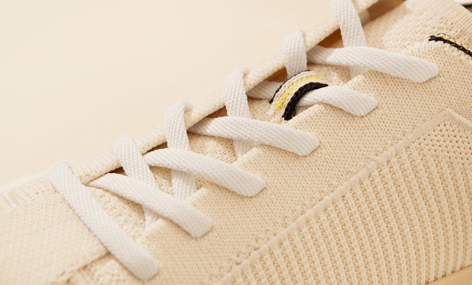 Close up of the laces of The Lace Up in Vanilla, showing the striped navy, yellow and white lace stay detail.