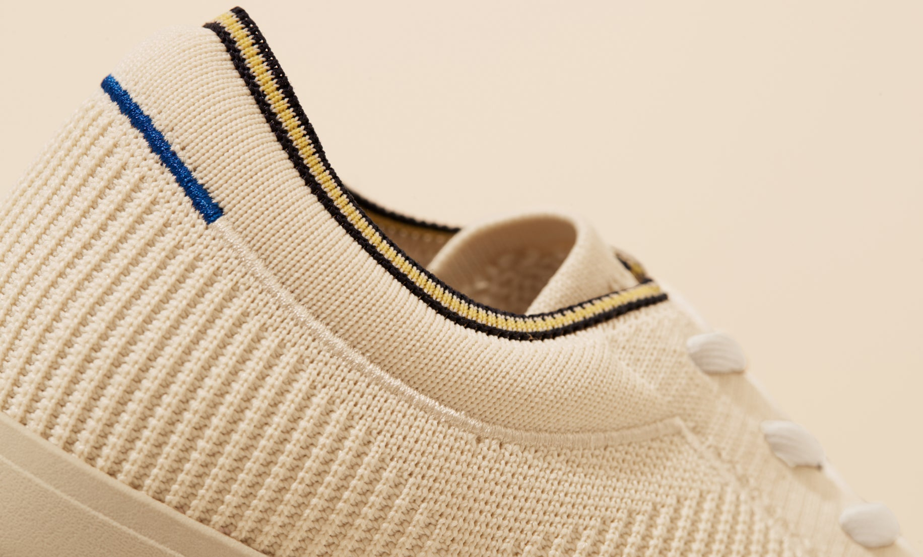 Close up of the plush ankle collar of The Lace Up in Vanilla, showing the navy and yellow striped ankle piping detail.