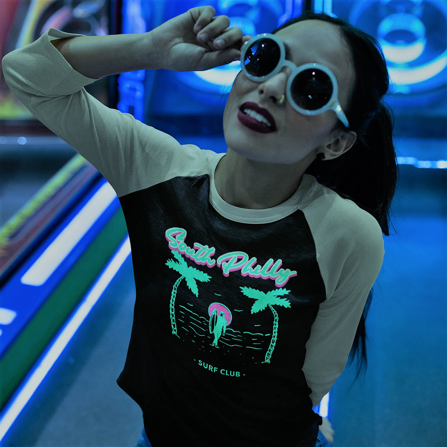 Cool Philly girl wearing a Phillygoat South Philly Surfers raglan tee in a neon arcade