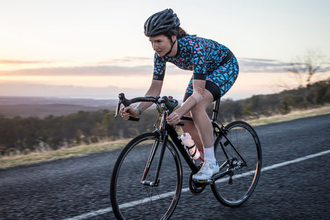 Female road cycling crouched in position to descend a hill wearing Fondo cycling kit