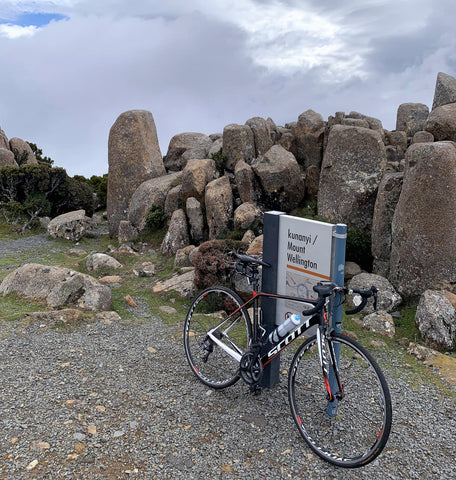 Image of the reviewer's bike at the summit of Mt Wellington / Kunyani. Bike is resting against the summit sign amongst large rock formation.  A beautiful end to a great bike ride